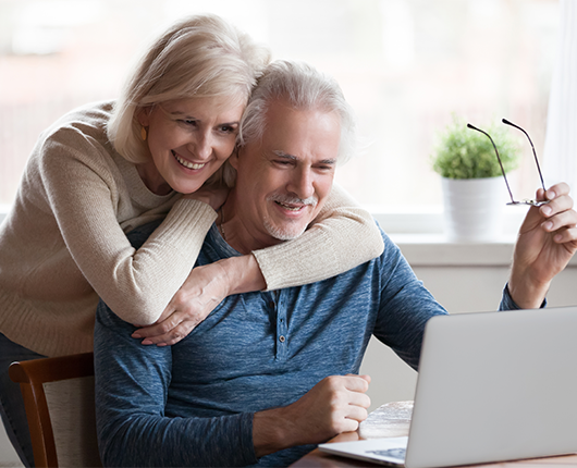 Woman hugging a man who is sitting down looking at a laptop.